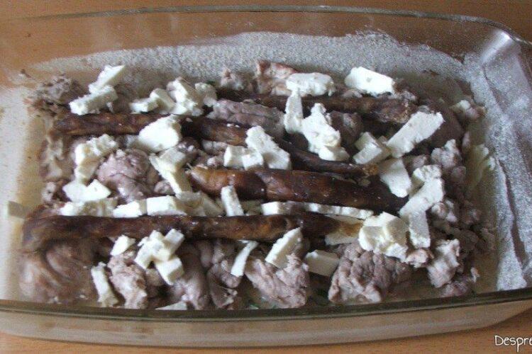 In vasul de copt sunt asezate bucati de creier, bucati de porcarele si cuburi de branza telemea de oaie.