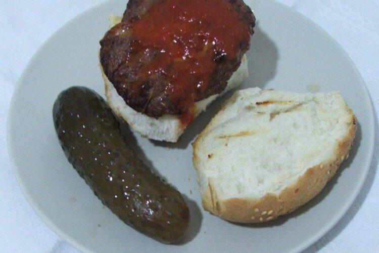 Hamburgher servit simplu, intr-o chifla, cu sos de rosii deasupra.