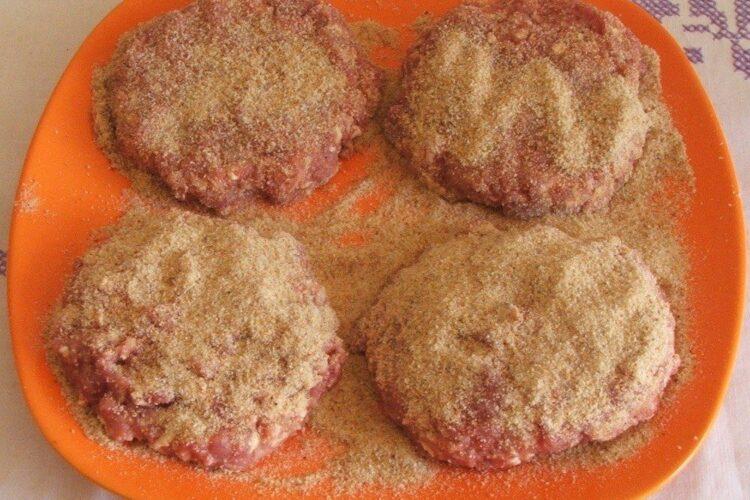Hamburgheri gata pregatiti pentru coacere in cuptorul incins al aragazului.