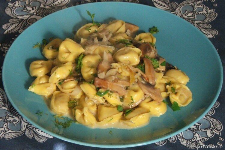 Tortellini umplute cu prosciuto in sos de praz, ciuperci si smantana - preparatul este gata servit.
