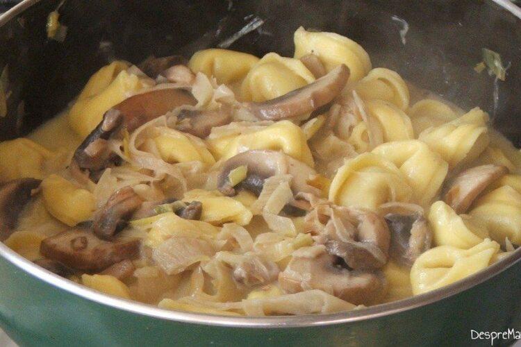 Adaugare tortellini fierte in tigaie peste amestecul de ciuperci, praz si smantana.