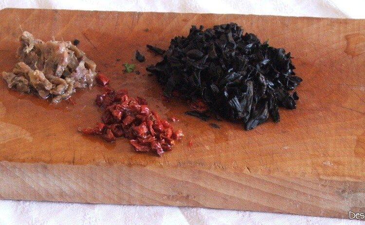 Tocare marunt, rosii uscate, ciuperci umflate in apa si file-uri de ansoa pentru calire in amestec de ulei de masline si unt proaspat.