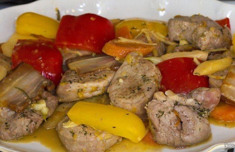 Muschiulet de porc cu legume si ciuperci la tigaie, in sos de smantana. Partea din carne, radacinoase si ardei gras a preparatului scoasa pe un platou.