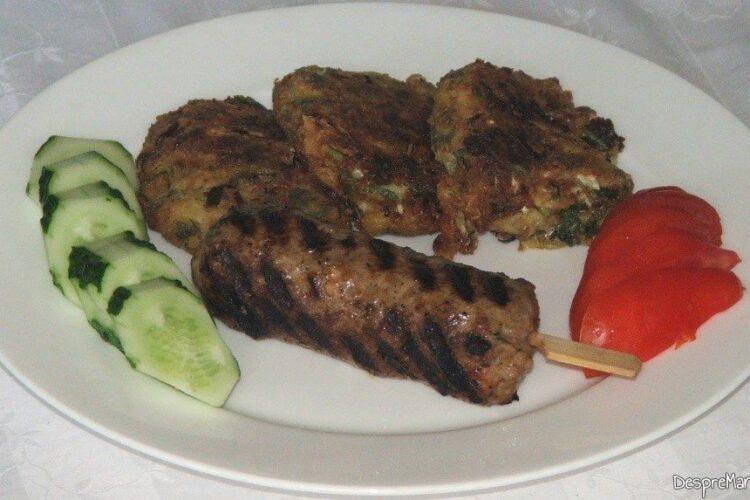 Chebab perpelit la gratar servit cu felii de rosii si felii de castraveti.