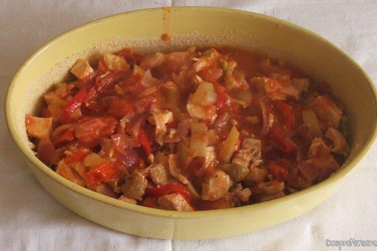 Strat format din bucatele din piept de pui gata copt si sos de rosii si ardei, adaugat in vasul de copt.