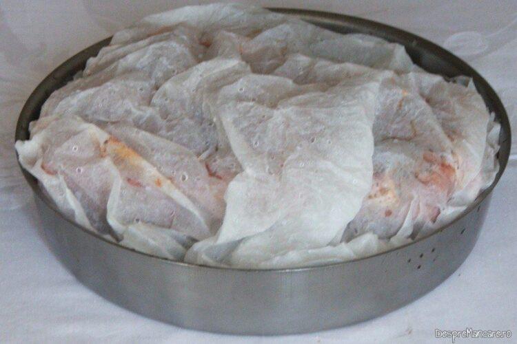 Tava de copt cu coaste de porc condimentate, acoperita cu hartie de copt umezita si stoarsa.