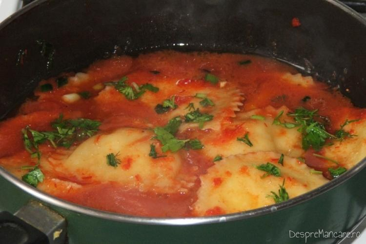 Adaugare paste umplute cu crab si creveti, fierte, in sosul de rosii.