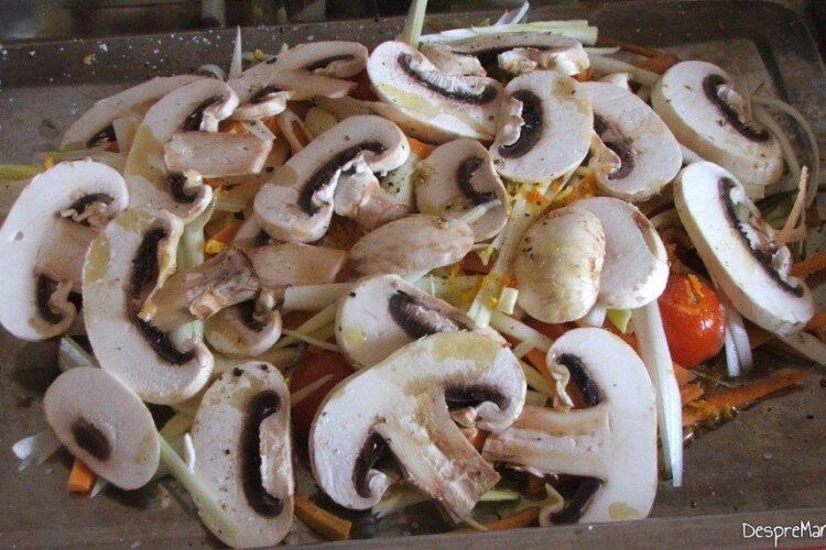 In tava de copt, deasupra legumelor se adauga ciupercile feliate si asezonate.
