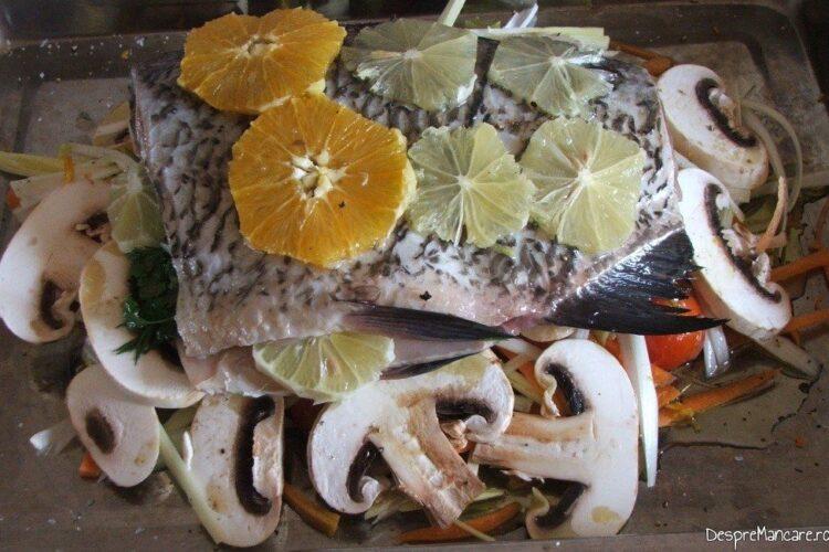 Trunchi de crap cu legume, ciuperci si citrice, pregatiti in tava pentru introducere la coacere in cuptorul aragazului.
