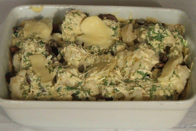 Strat de branzaturi si felii de mozarella puse pe deasupra buchetelelor de conopida si ciuperci calite din vasul de copt.
