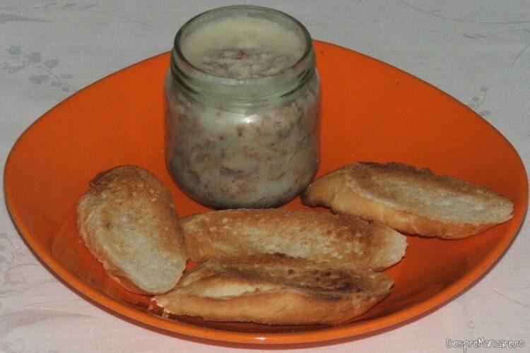 Borcan cu pasta tartinabila din pecie de porc si felii de paine prajita pentru servire aperitiv.