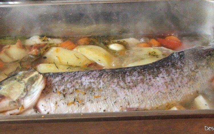 Stiuca intreaga care fierbe in tava de copt cu legume si condimente.