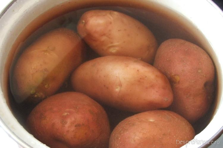 Cartofi rosii pusi la fiert in apa rece cu sare grunjoasa.