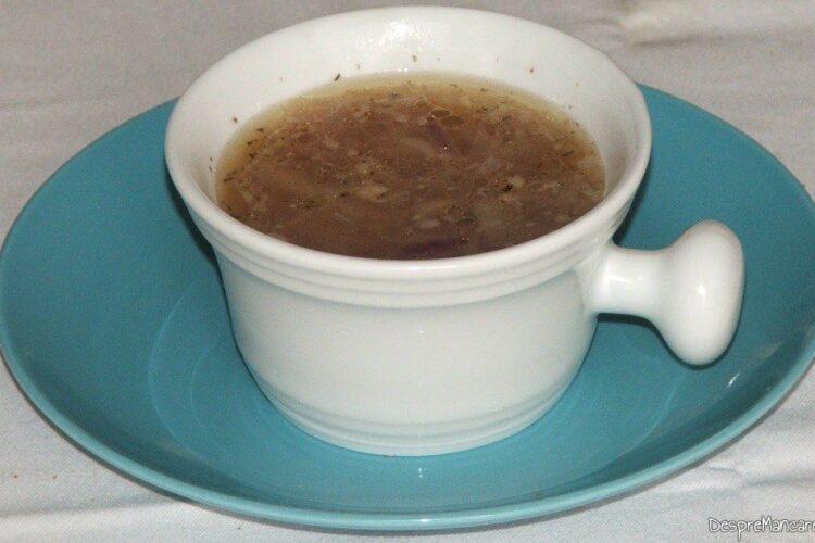 Zeama din ceapa si apa calda turnata in bol de ceramica.
