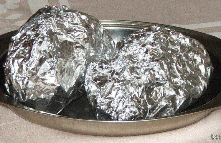 Cartofi rosii zimtati si impanati, impaturiti in folie din staniol pregatiti pentru coacere.