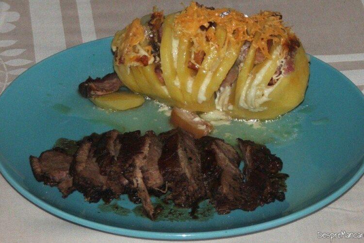 Felii din pulpa de capra cu cartofi zimtati, impanati, la cuptor - preparatul este gata servit.