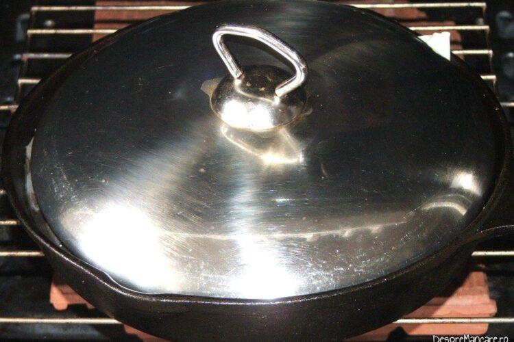Tigaia din fonta cu ingrediente, acoperita cu capac introdusa in cuptorul aragazului, la foc potrivit.