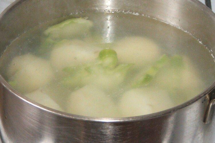 Fierbere felii de cartofi noi si felii din tulpina de brocoli in apa cu sare grunjoasa.