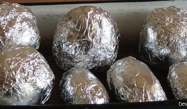 Sfecle si cartofi intregi, invelite(i) puse(i) in tava de copt pentru coacere in cuptorul aragazului.