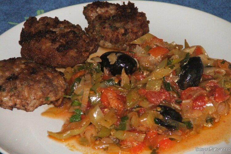 Mancare de praz cu masline servita langa chiftelute din carne tocata.