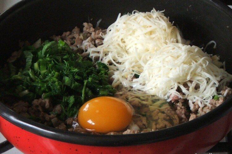 Amestecare carne tocata calita cu cascaval afumat, oua si verdeata.