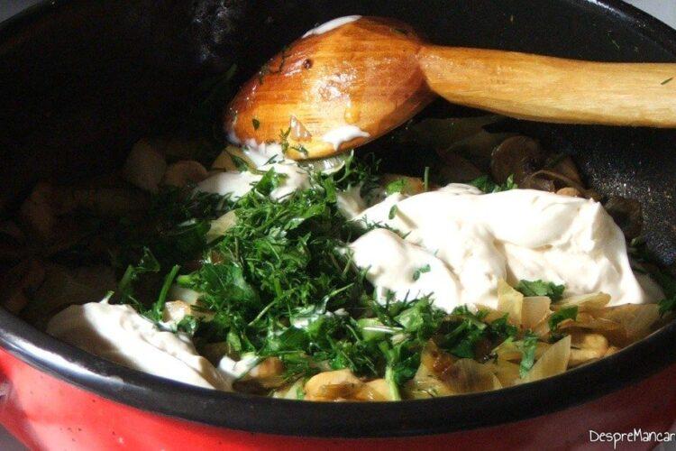 Adaugare smantana grasa si verdeata tocata in tigaia cu praz si ciuperci calite.