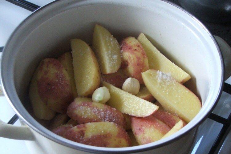 Cartofi noi, rosii, pusi la fiert in apa rece cu sare grunjoasa si 2 catei de usturoi.