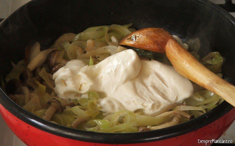 Adaugare smantana grasa in amestecul de praz, ciuperci si usturoi, calite.