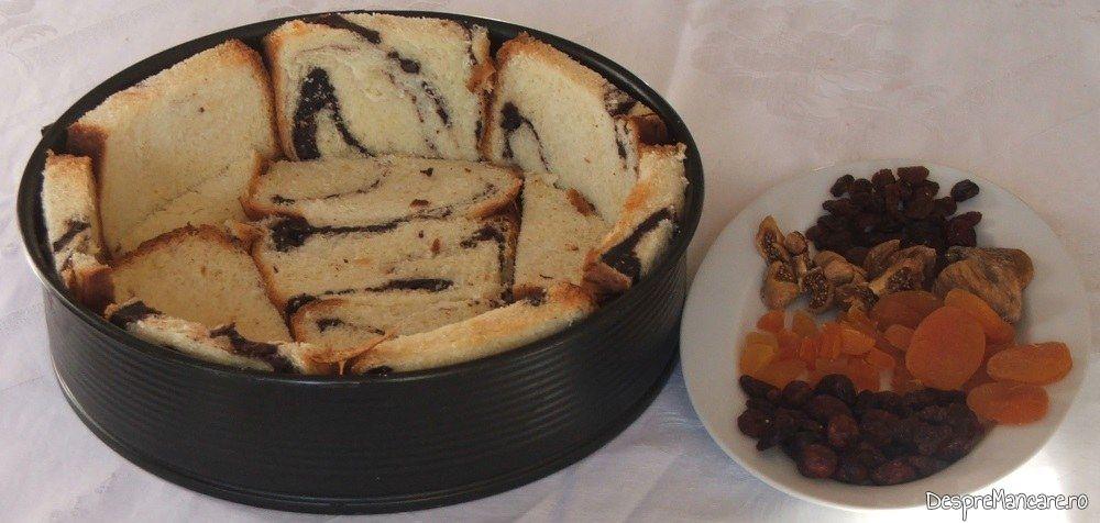 Tava de tort se tapeteaza cu felii de cozonac. Fructe uscate puse la indemana.