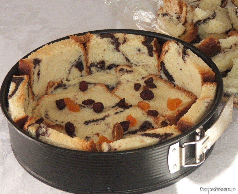In forma de copt tort cu cozonac inmuiat in amestec de lapte dulce, smanatana si oua de gaina se adauga fructele uscate.