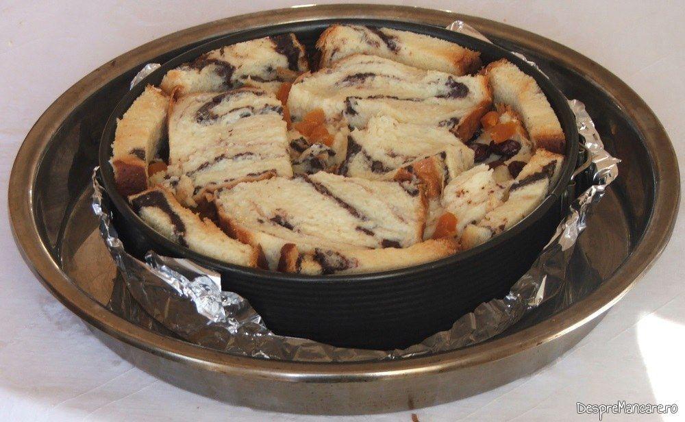 Forma de copt cu tort din cozonac invechit imbibat in amestec de oua de gaina, lapte dulce si smantana grasa pregatit pentru intorducere in cuptorul aragazului.