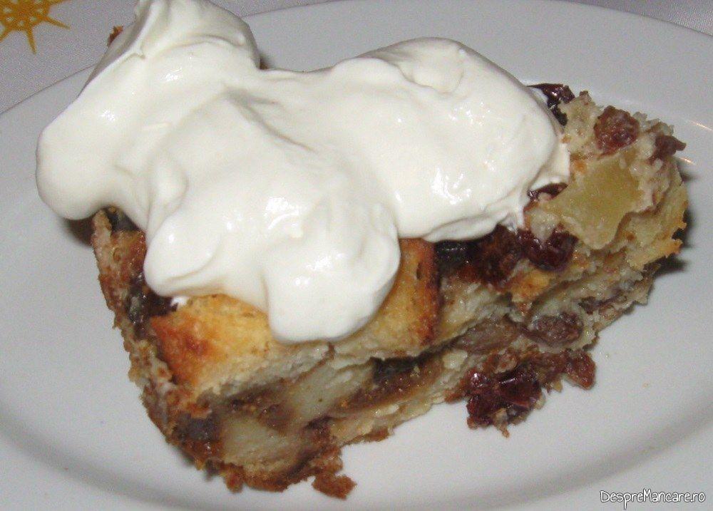 Felie de tort din cozonac cu fructe uscate si frisca gata servita.