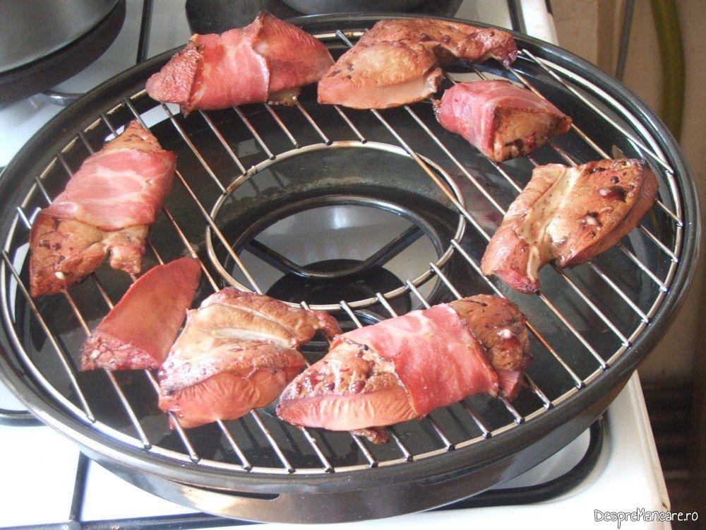 Fasii de ficat de vitel condimentate si invelite in prosciuto, asezate pe gratar pentru a se frige.